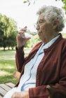 Haute femme assis sur un banc de parc, verre d'eau à boire — Photo de stock