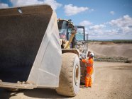 Arbeiter spricht Baggerfahrer im Steinbruch an — Stockfoto
