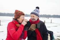 Couple having hot drink in snow — Stock Photo