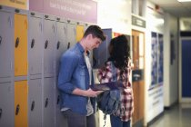 Young male student revising from file in college locker room — Stock Photo