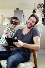 Father and son in bat mask sitting on chair with digital tablet — Stock Photo