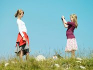 Fille prendre photo de ami à l'extérieur — Photo de stock