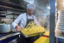 Шеф-кухар готує свіжоприготовані макарони в традиційній італійській кухні ресторану — стокове фото