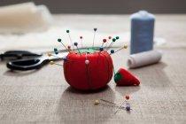 Nadelkissen mit Fäden und Schere auf Tisch — Stockfoto