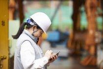 Працівник з використанням смартфона на суднобудівному заводі, Goseong-Gun, Південна Корея — стокове фото