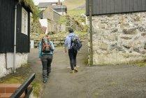 Excursionistas pasando pueblo, Vagar, Islas de Faroe - foto de stock