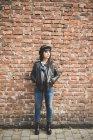Jeune femme devant un mur de briques — Photo de stock