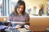 Mature woman using touchscreen on digital tablet in wine bar — Stock Photo