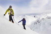 Alpinistes ascendant montagne couverte de neige, Saas-Fee, Suisse — Photo de stock