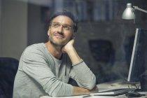 Empresário na mesa olhando pela janela do escritório — Fotografia de Stock
