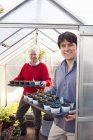 Father and adult son holding plants in greenhouse — Stock Photo