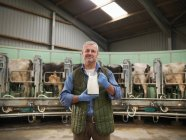 Portrait of farmer holding jug of milk in rotary milking parlour on dairy farm with cows — Stock Photo