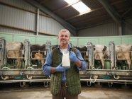 Porträt von Bauer hält Krug Milch in rotary Melkstand auf Milchviehbetrieb mit Kühen — Stockfoto