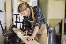 Молодая ремесленница с помощью калькулятора в трубной мастерской — стоковое фото