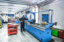 Engineer preparing industrial lathe in engineering factory — Stock Photo