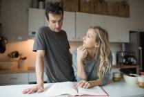 Пара чтение рецепт книги на кухне — стоковое фото