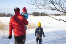 Father and two sons walking in snow covered landscape, rear view — Stock Photo
