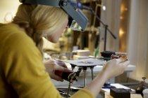 Joyería femenina usando soplete en miniatura en el estudio de diseño - foto de stock