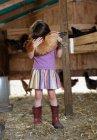Девушка держит курицу в курятнике — стоковое фото