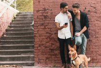 Young male couple leaning against wall and reading smartphone — Stock Photo