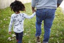 Вид сзади человека, прогуливающегося рука об руку с дочерью в саду — стоковое фото