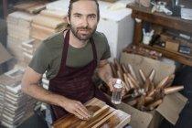 Ritratto di uomo che applica la macchia di legno al tagliere in fabbrica — Foto stock