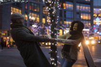 Romantic happy couple enjoying city during winter holidays spinning around tree with holidays lights — Stock Photo