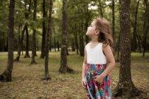 Jeune fille debout dans la forêt et le levant — Photo de stock