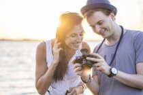 Young couple looking at camera by sea at sunset — Stock Photo