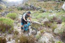 Young man mountain biking through scrubland — Stock Photo