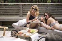 Mujeres relajándose y comiendo frutas en tumbona, Amagansett, Nueva York, EE.UU. - foto de stock