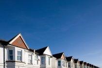Tapas de casas contra el cielo azul - foto de stock