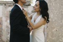 Жених и невеста на улице, невеста выпрямляет шейный галстук жениха — стоковое фото