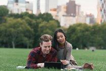 Casal adulto médio em cobertor de piquenique leitura tablet digital em Central Park, Nova York, EUA — Fotografia de Stock