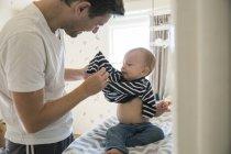 Отец одевает сына дома — стоковое фото