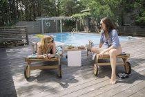 Женщины расслабляются и болтают на шезлонгах, Амагансетт, Нью-Йорк, США — стоковое фото