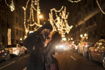 Romantic happy couple enjoying city during winter holidays kissing under holiday lighting — Stock Photo