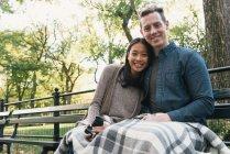 Ritratto di coppia adulta seduta sulla panchina del parco con fotocamera reflex — Foto stock