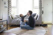 Father and young son at home, playing together — Stock Photo