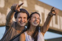 Happy young couple pointing into distance in front of signboard — Stock Photo