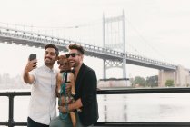 Young male couple on riverside taking smartphone selfie with dog, Astoria, New York, USA — Stock Photo