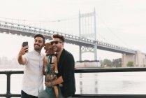 Jeune couple masculin au bord de la rivière prenant smartphone selfie avec chien, Astoria, New York, USA — Photo de stock