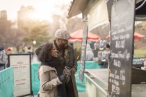 Romantic happy couple enjoying city during winter holidays at park refreshment stand — Stock Photo