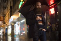 Man walking in city at night, using umbrella, Downtown, San Francisco, California, USA — Stock Photo