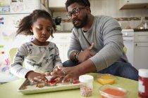 Padre e hija decorando galletas sin cocer - foto de stock