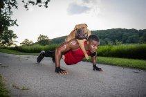 Молодой человек отжимается на сельской дороге, давая собаке спираль. — стоковое фото