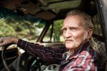 Portrait of senior man sitting inside car — Stock Photo