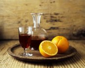 Red wine decanter, glass and fresh orange fruit halves on wooden tray — Stock Photo