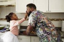 Fille nourrir père dans la cuisine — Photo de stock