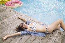 Woman relaxing beside swimming pool, Amagansett, New York, USA — Stock Photo